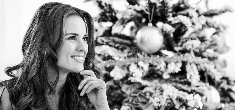 坐在圣诞树附近的体贴的少妇 免版税库存照片