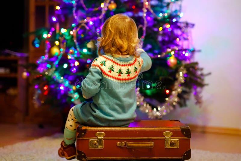坐在圣诞树附近的可爱的小孩女孩 演奏和装饰与家庭的小孩xmas树 ?? 免版税图库摄影