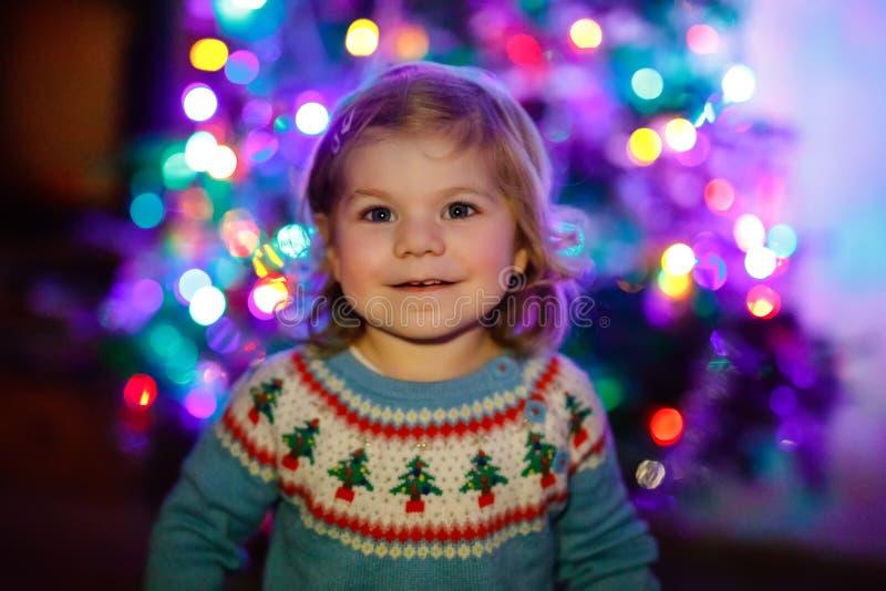 坐在圣诞树附近的可爱的小孩女孩 演奏和装饰与家庭的小孩xmas树 ?? 库存图片