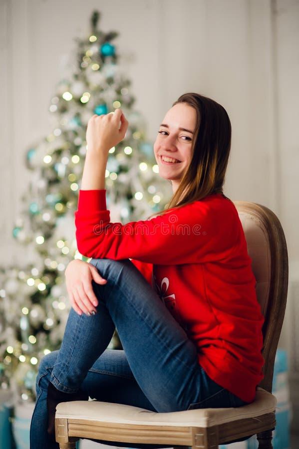 坐在圣诞树附近的愉快的少妇 库存照片