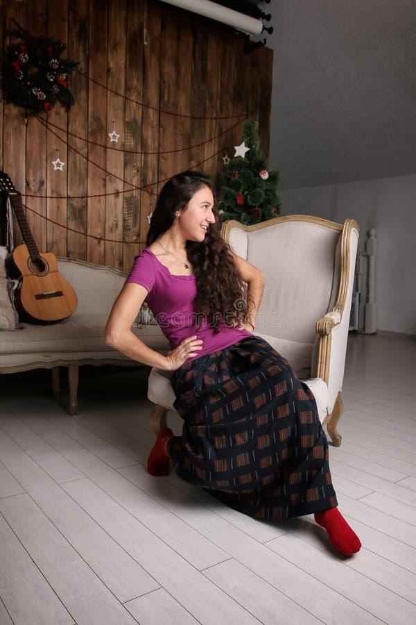 坐在圣诞节内部和等待的庆祝的椅子的年轻西班牙妇女 图库摄影