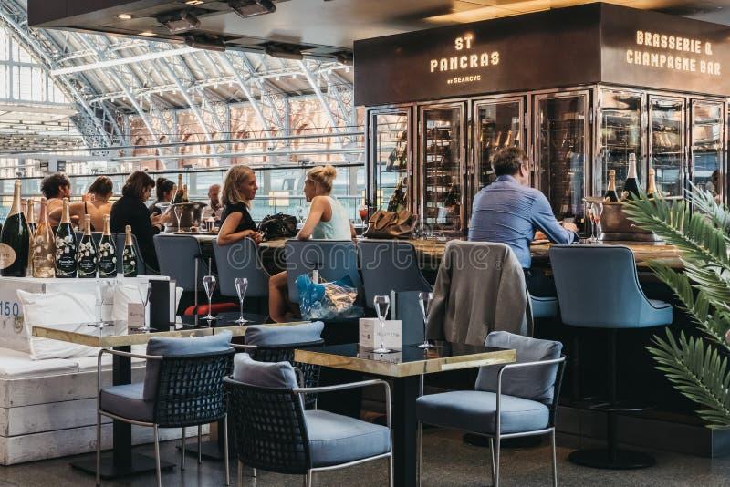 坐在圣Pancras驻地,伦敦,英国里面的一个酒吧的人们 图库摄影