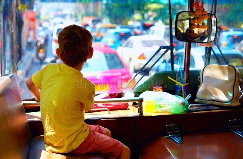 坐在地方公开公共汽车上的年轻男孩,当游遍市曼谷时 库存图片