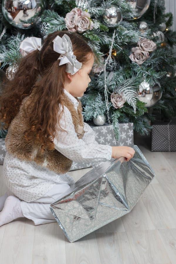 坐在地板的小孩女孩在与圣诞节礼物的圣诞树附近在手 免版税库存照片