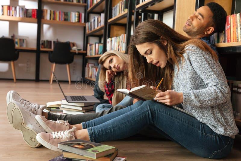坐在地板阅读书的图书馆里的被集中的学生 免版税库存照片