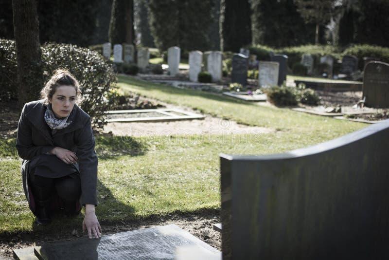 坐在坟墓的妇女 免版税图库摄影