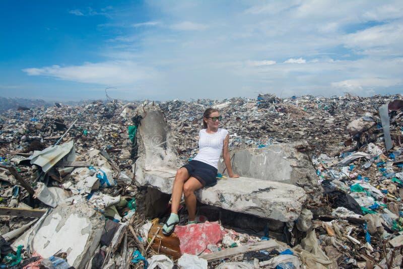坐在垃圾中的年轻欧洲妇女在垃圾堆 免版税库存图片