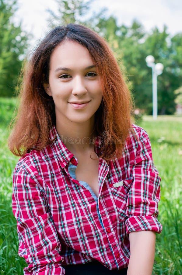 坐在城市公园的少年红头发人女孩 免版税库存图片