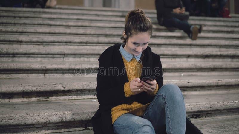 坐在城市和用途智能手机的梯子的年轻可爱的妇女 发短信与朋友的学生女孩 免版税库存照片
