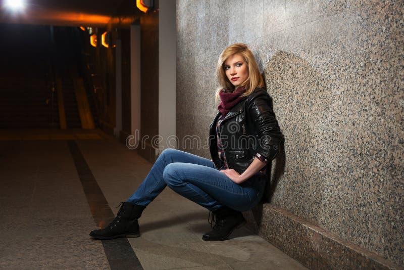 坐在墙壁的皮夹克的年轻时尚妇女 免版税图库摄影