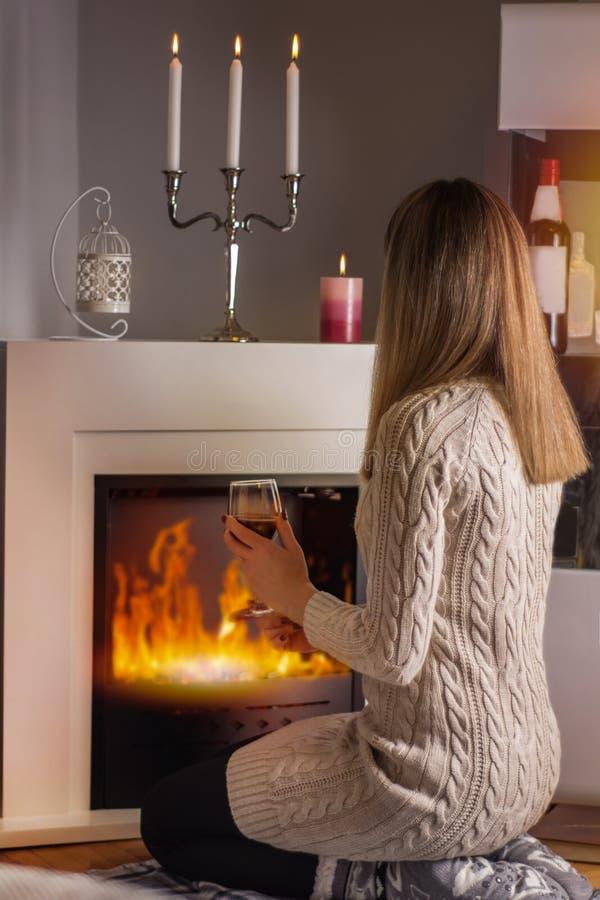 坐在壁炉前面和温暖与红酒酒杯的女孩在手上 免版税库存照片