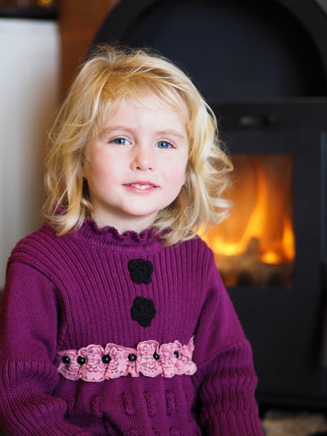 坐在壁炉前面的白肤金发的蓝眼睛的小女孩 免版税库存图片