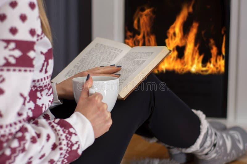坐在壁炉和看书和饮用热的茶前面的少女 免版税库存照片