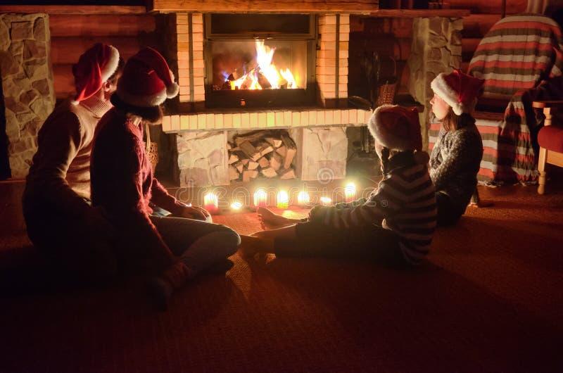 坐在壁炉附近和庆祝圣诞节和新年、父母和孩子圣诞老人帽子的愉快的家庭 免版税库存照片