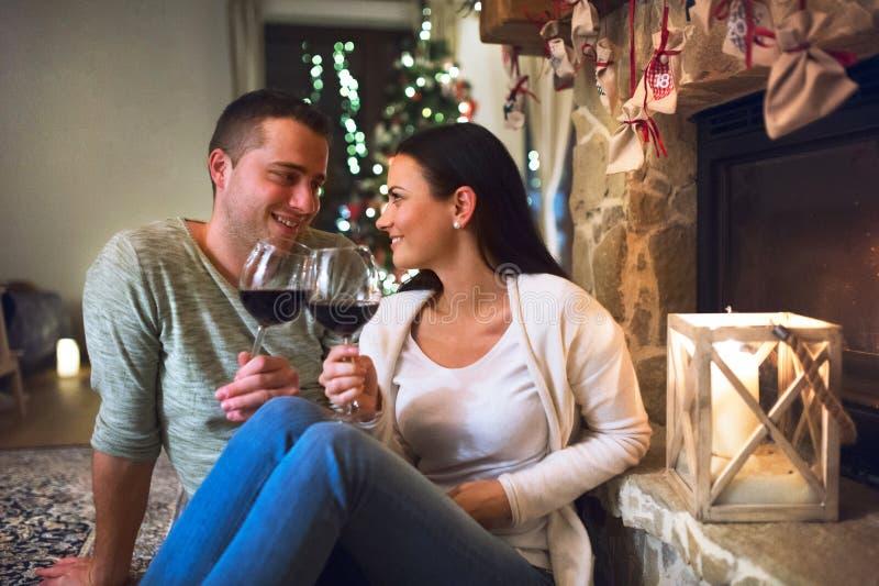 坐在壁炉,饮用的酒前面的夫妇 免版税库存图片
