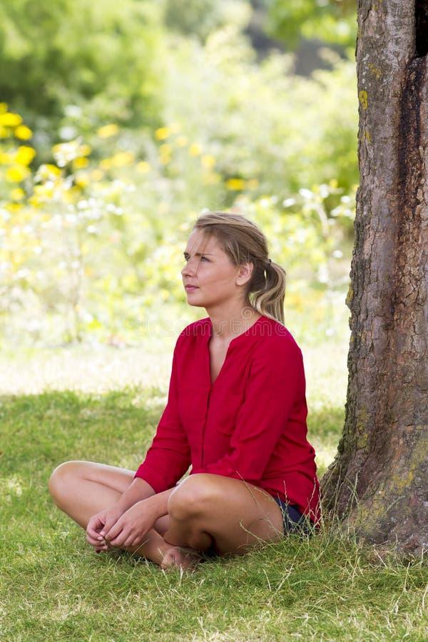 坐在夏天生气勃勃的一棵树下的孤独的少妇 免版税库存图片