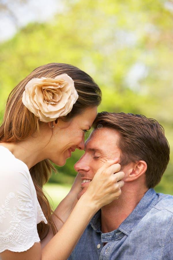 坐在夏天花的域的浪漫夫妇 免版税库存图片