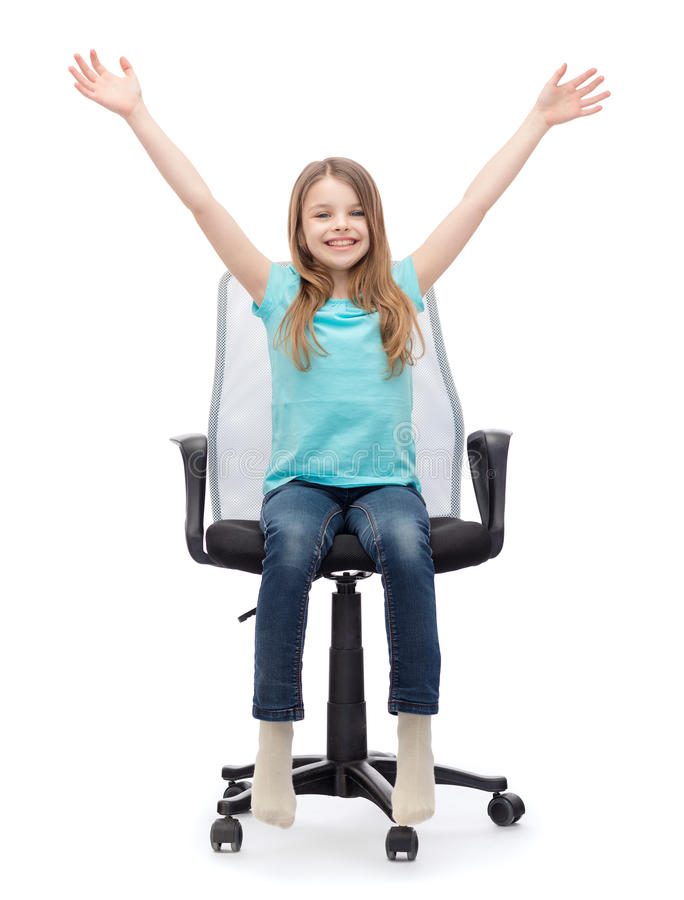 坐在大办公室椅子的微笑的小女孩 库存照片