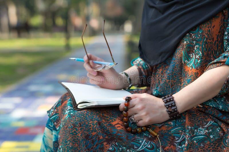 坐在大学公园和做手笔记的阿拉伯学生 免版税库存照片