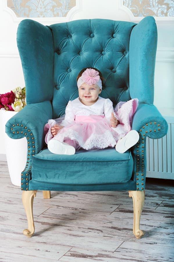 坐在大椅子的愉快的年轻婴儿女孩 免版税库存图片