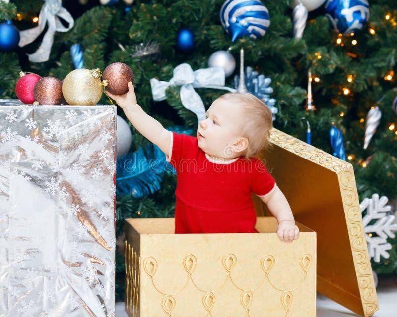 坐在大礼物礼物箱子的红色假日礼服的滑稽的微笑的白种人女婴小孩在新年树下 免版税库存图片