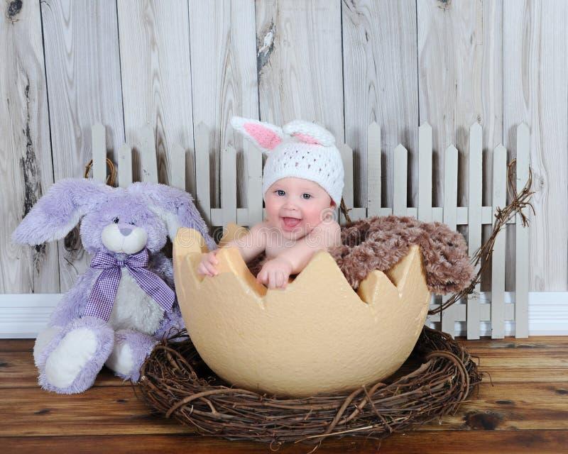 坐在大鸡蛋的兔宝宝帽子的可爱的婴孩 免版税库存照片
