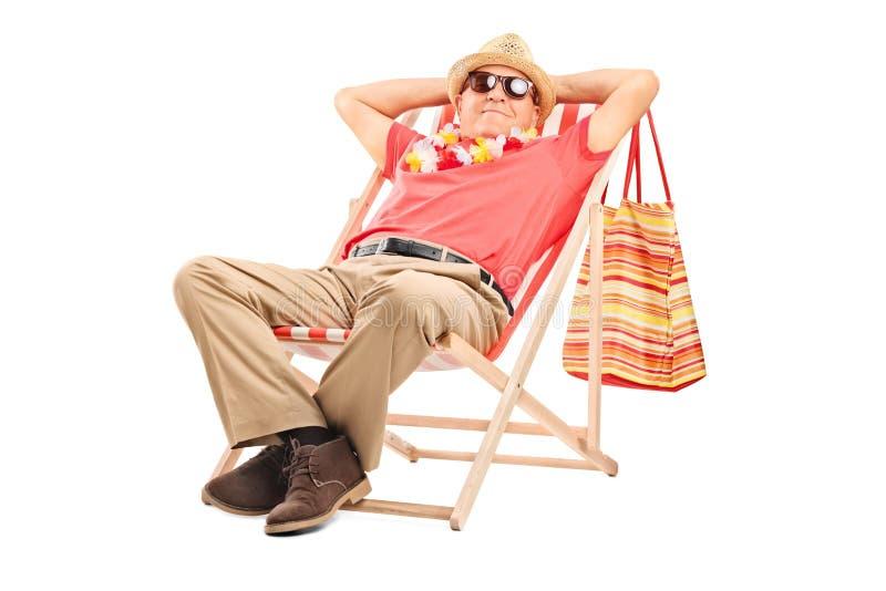 坐在太阳懒人椅子的资深绅士 库存照片