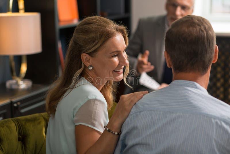 坐在她的丈夫旁边的微笑的愉快的妻子 免版税库存照片