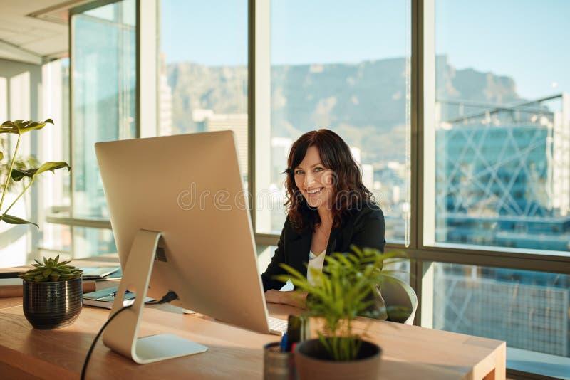 坐在她的书桌的微笑的少妇 免版税库存图片