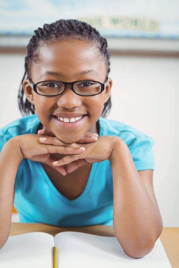 坐在她的书桌的逗人喜爱的学生在教室 免版税库存照片