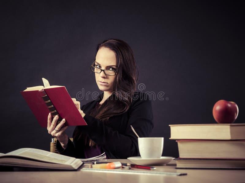 坐在她的书桌读书的老师 图库摄影