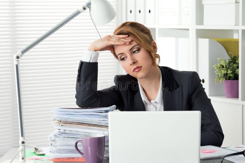 坐在她的办公室的疲乏的女实业家画象 免版税库存图片
