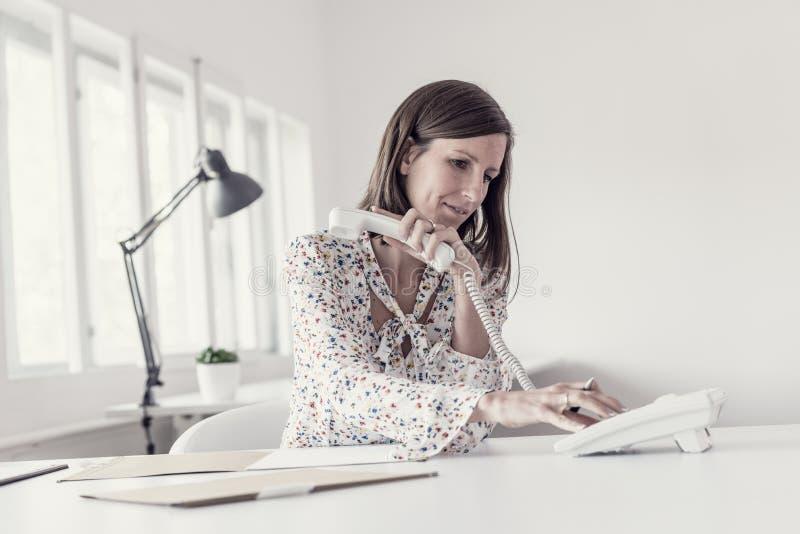 坐在她的办公桌的年轻女实业家做telephon 免版税库存照片