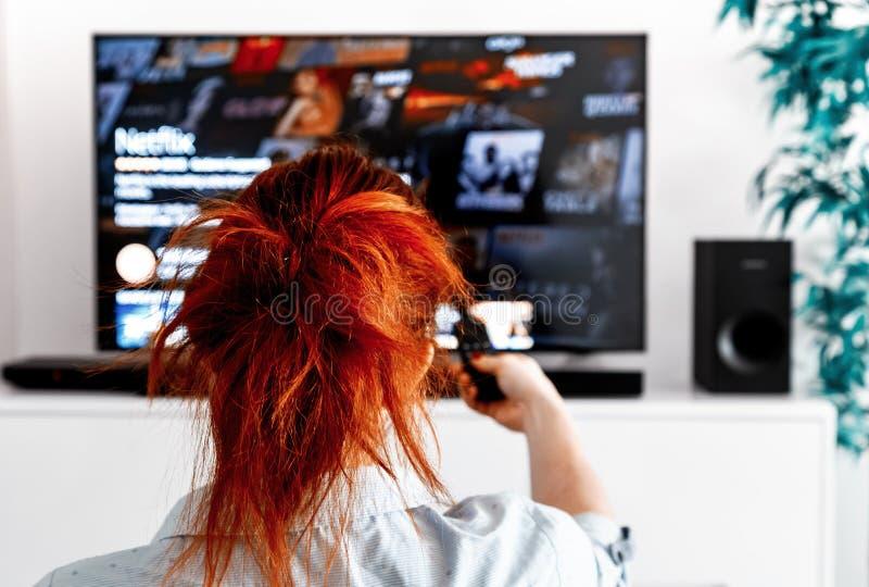 坐在她的客厅的红头发人妇女拿着电视遥控和显示netflix 库存照片