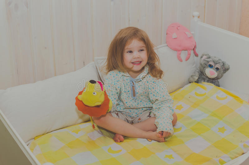 坐在她的小儿床的女婴 库存照片