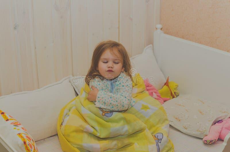 坐在她的小儿床的女婴 免版税图库摄影