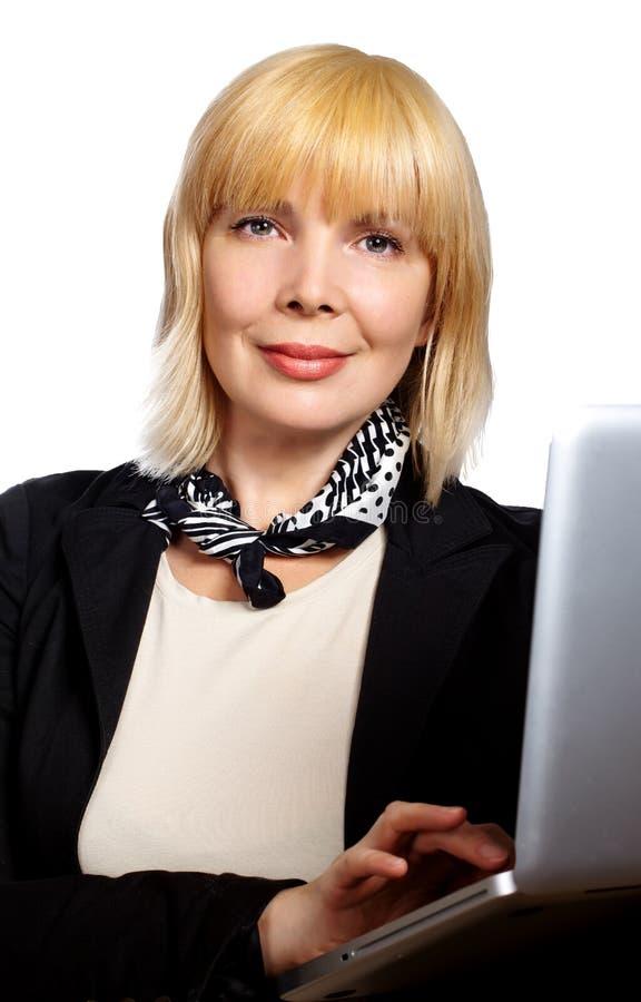 坐在她的有la的书桌的一名俏丽的女实业家的画象 库存照片