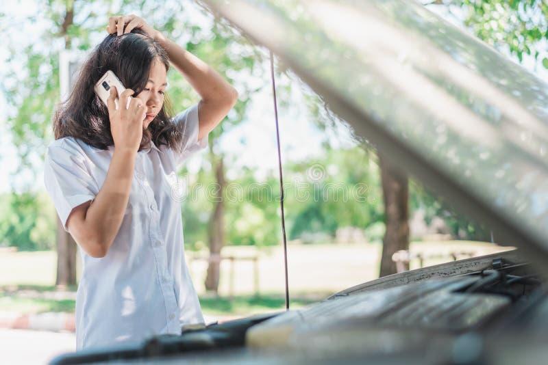 坐在她的汽车前面的年轻亚洲妇女,尝试对呼吁与她的汽车的协助身体垮下来 免版税库存照片