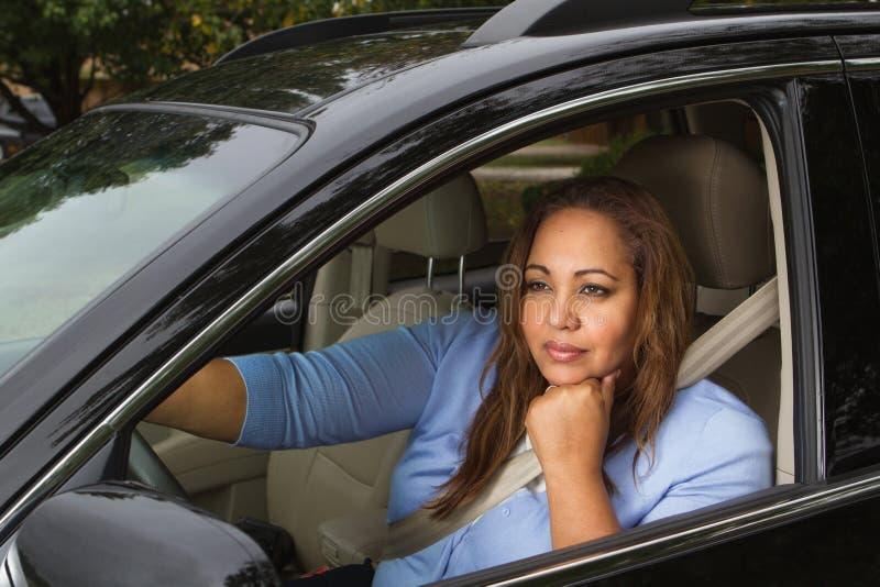 坐在她的汽车的妇女 免版税库存图片