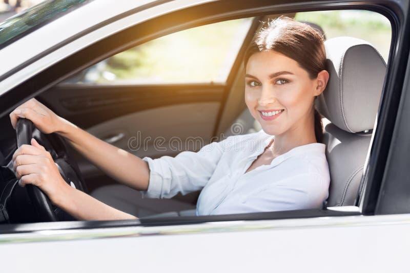 坐在她的汽车的年轻女商人 免版税库存图片