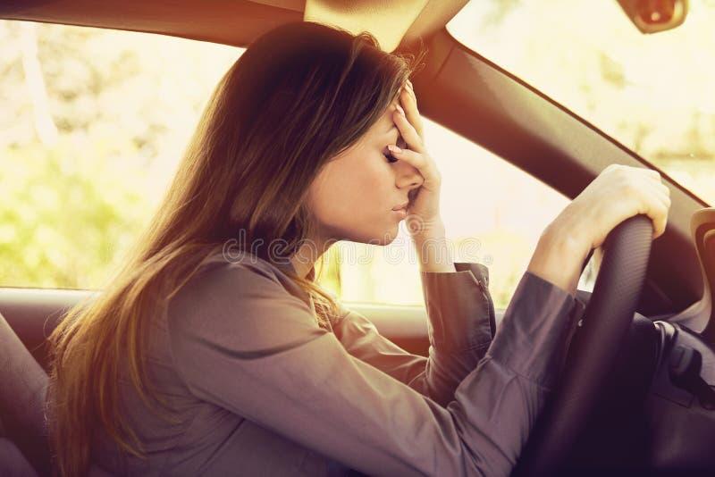 坐在她的汽车里面的被注重的妇女司机 免版税库存图片