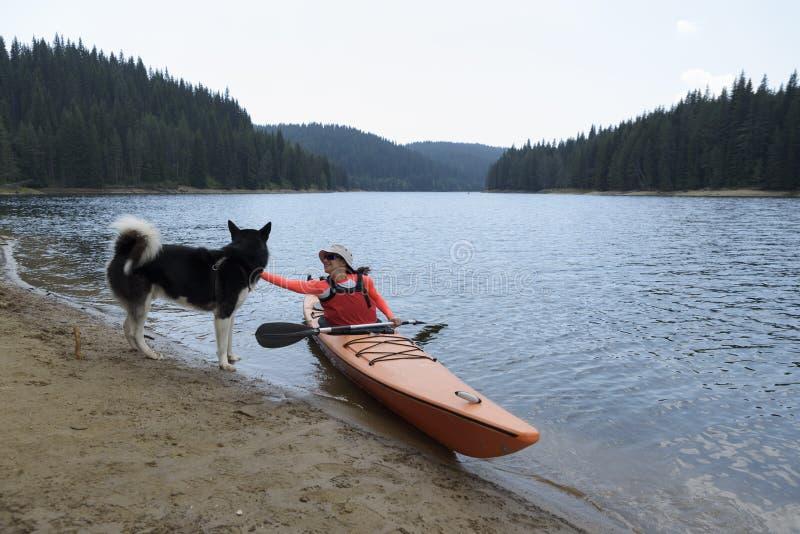 坐在她的皮船的少妇爱抚阿拉斯加的爱斯基摩狗 免版税库存图片