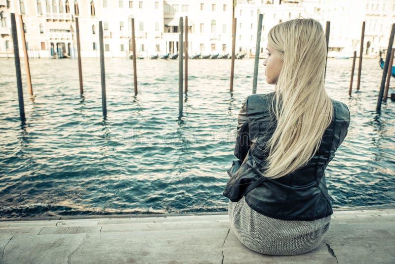 坐在威尼斯的白肤金发的女孩 免版税库存照片