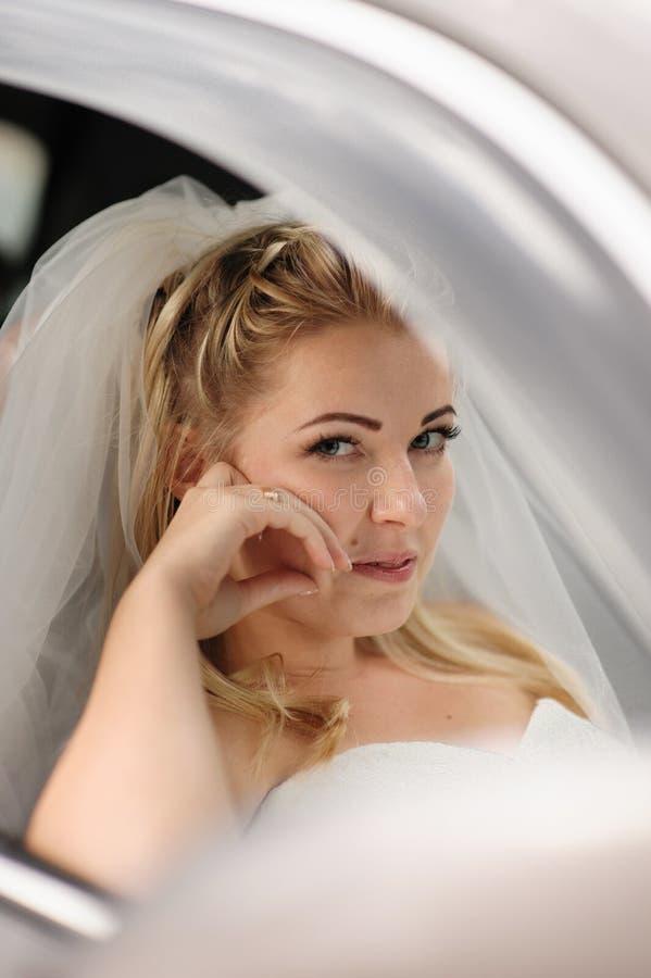 坐在婚礼汽车的愉快的新娘 免版税库存照片