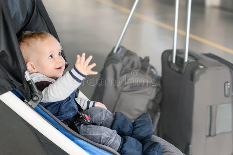 坐在婴儿推车的逗人喜爱的滑稽的白种人男婴靠近行李在机场终端 儿童有suitcasese的罪孽支架 免版税图库摄影