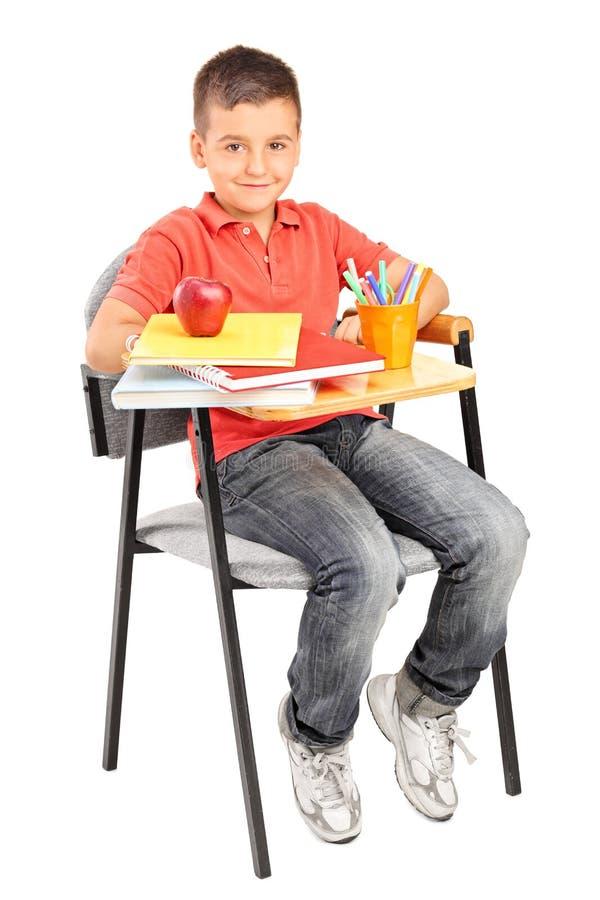 坐在学校书桌的男小学生 免版税库存图片
