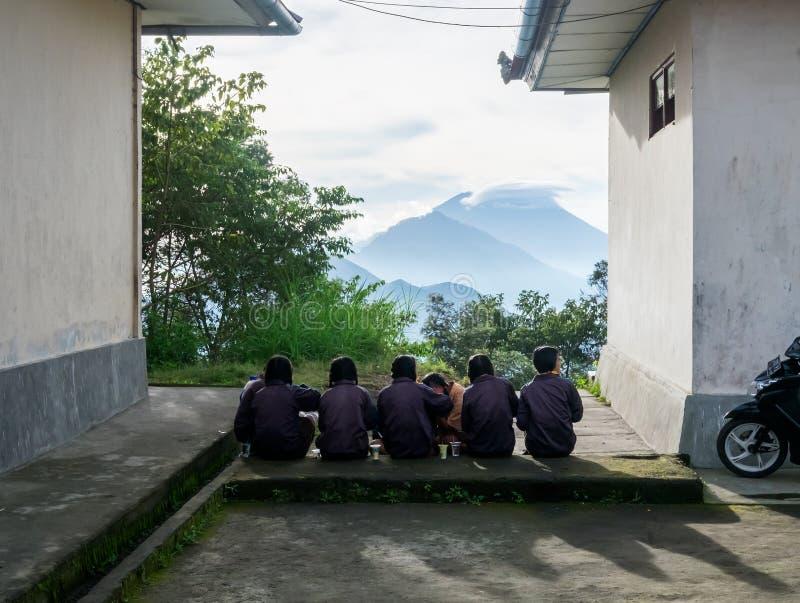 坐在学校附近的印度尼西亚孩子 库存照片