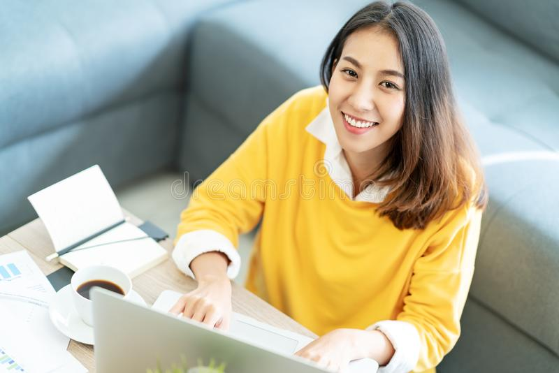 坐在客厅地板的年轻可爱的愉快的亚裔女学生微笑和看照相机 免版税库存图片