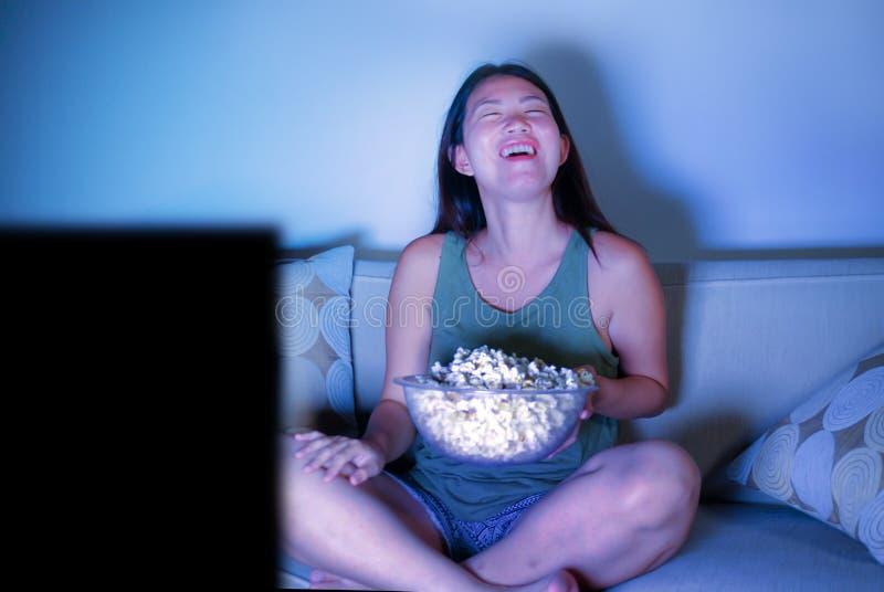坐在客厅沙发长沙发观看的电视喜剧夜间吃popc的年轻俏丽和愉快的亚裔韩国妇女 图库摄影