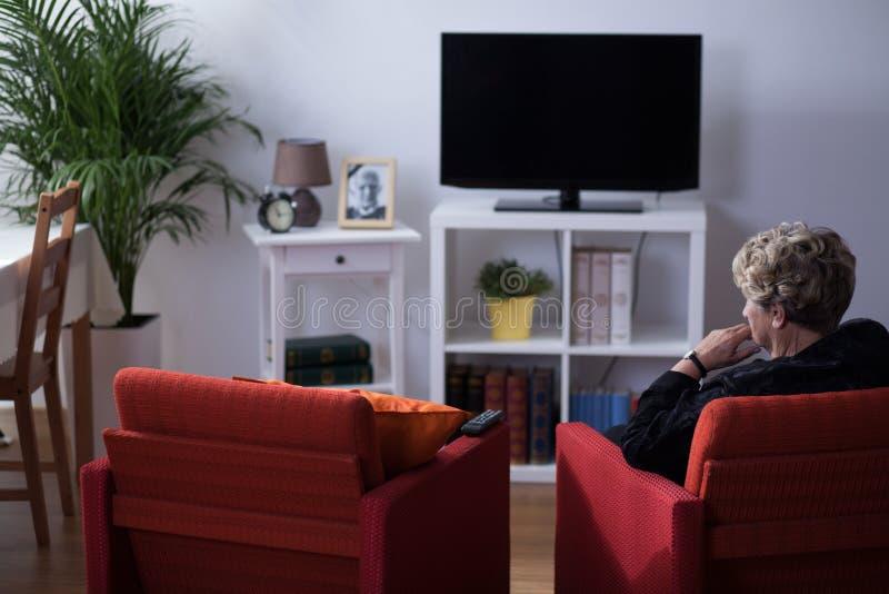 坐在客厅的寡妇 免版税库存图片
